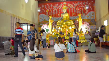 budismo : AYUTTHAYA. THAILAND - CIRCA FEB 2015: Buddhist worshippers kneel and pray before a gilded image of the Buddha at a temple inside Ayutthaya Historical Park in Thailand.