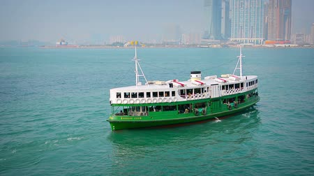 паром : HONG KONG. CHINA - CIRCA JAN 2015: Green and white ferry. called the Morning Star. cruises in Victoria Harbor with a load of passengers. with Hong Kongs skyline in the background.