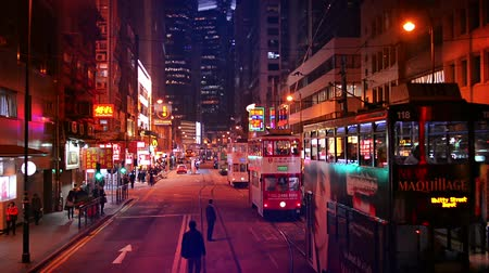 felhőkarcoló : HONG KONG. CHINA - CIRCA JAN 2015: Nighttime traffic along a major city street in downtown Hong Kong. with double decker cable cars and highrise buildings.