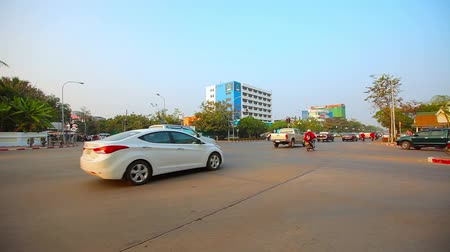 editorial : VIENTIANE. LAOS - CIRCA DEC 2013: Typical morning traffic at a central intersection in Vientiane. Laos. on a clear. sunny day. Stock Footage