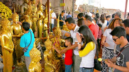 budist : AYUTTHAYA. THAILAND  CIRCA FEB 2015: Buddhist worshippers press gold leaf onto images of the Buddha as an offering and pray at an alter at a large temple compex in Ayutthaya. Thailand. Stok Video