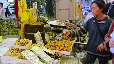 nekvalitní potraviny : HONG KONG. CHINA  CIRCA JAN 2015: Local street food vendor cooking and selling chestnuts. sweet potatoes and other roasted snacks from a mobile cart in downtown Hong Kong.