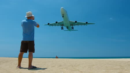 final destination : Video 3840x2160  Photographer shooting a large. commercial airliner as it cruises low over a beach on final landing approach to Phuket International Airport in Thailand. Stock Footage