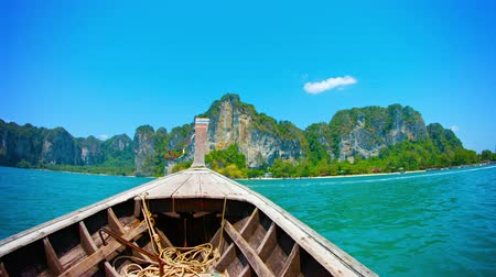 outside view : UltraHD video  Cruising towards the limestone cliffs overlooking a tropical island. on a handmade wooden boat with an improvised engine. Stock Footage