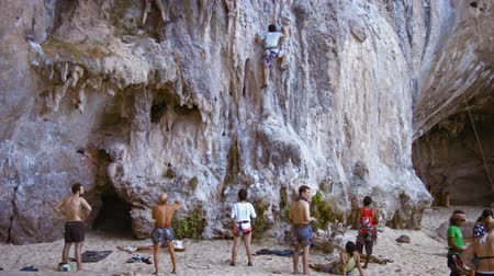 řádek : RAILAY BEACH. THAILAND  CIRCA FEB 2015: Brave tourist attempting to scale the limestone cliff face at Railay Beach. a popular tourist destination in Thailand.