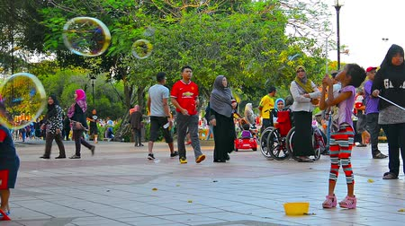 KUALA LUMPUR. MALAYSIA  CIRCA FEB 2015: Children playing with bubbles at Titiwangsa Lake Garden. a beautiful and popular city park in downtown Kuala Lumpur. Malaysias capital city. Стоковые видеозаписи