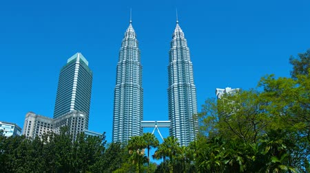 identical : KUALA LUMPUR. MALAYSIA  CIRCA FEB 2015: The iconic Petronas Twin Towers. standing against a clear blue sky. as seen from Kuala Lumpur City Centre Park. in Malaysias capital city.