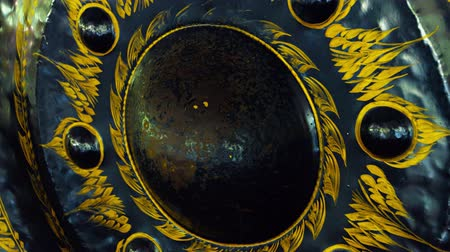 kedah : UltraHD video  Beautiful. handpainted surface of an antique steel gong. with intricate decorations in yellow. hanging in Wat Tham Kisap Temple in Langkawi. Malaysia