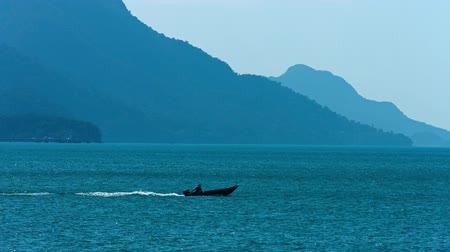 ryba : Small. motorized fishing boat. crossing the choppy surface of a tropical bay with forested mountains in the background. Dostupné videozáznamy
