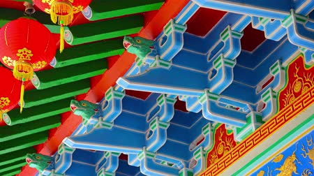 motívum : Intricate and traditional ornamentation inside a Chinese Buddhist temple including bold colors. paper lanterns and a dragon motif.