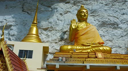запутанный : LANGKAWI. MALAYSIA - CIRCA FEB 2015: Big. gold colored buddha statue outside Wat Tham Kisap. a Thai temple in Langkawi Malaysia.