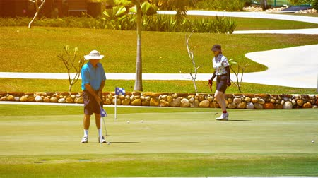 kedah : LANGKAWI. MALAYSIA - CIRCA FEB 2015: Pair of golfers putting on a green at the Gulf Club. Datai Bay in Langkawi Malaysia. as golf carts cruise by in the background