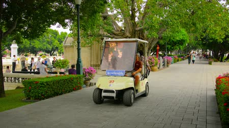 király : AYUTTHAYA. THAILAND - CIRCA NOV 2013: Tourists move through the park on foot and by electric vehicles. Bang Pa-In Palace