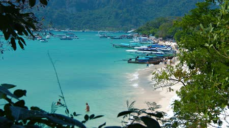 speedboats : Video 1080p - Dozens of tour boats line the sandy beach and crowd the waters of a beautiful tropical bay in Southern Thailand. Stock Footage