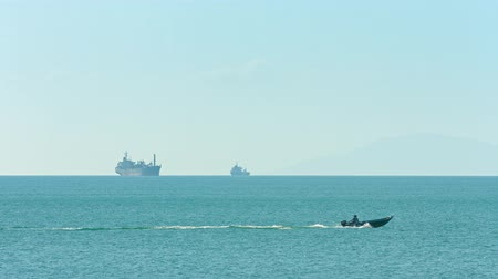oceânico : Video 3840x2160 - Small motorboat skims over a flat expanse of tropical sea. with two enormous commercial ships standing against the distant horizon. Stock Footage
