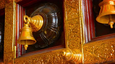 filigrana : Video UltraHD - Beautiful. decorative. ceremonial bells. mounted on a door  in a Hindu temple. with intricately detailed. gilded tracery all around. Vídeos