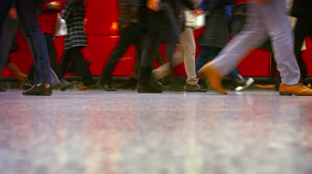 çini : HONG KONG. CHINA - CIRCA JAN 2015: Low angle shot of the legs and feet of commuters walking through a crowded. urban subway station in downtown Hong Kong. China. Stok Video