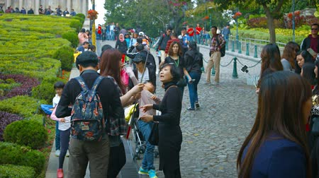 outside : MACAU. CHINA - CIRCA JAN 2015: Tourists employing selfie sticks to take photos in front of the ruins of Sao Paulo Cathedral in Macau. China.