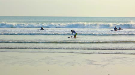 waders : KUTA. BALI. INDONESIA - CIRCA JUL 2015: Tourists try their luck at surfing as row upon row of small breakers roll onto a tropical beach in Kuta. Bali.