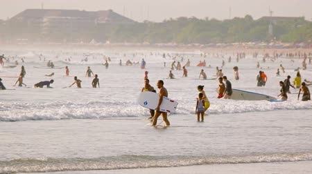 waders : KUTA. BALI. INDONESIA - CIRCA JUL 2015: Dozens of surfers. body boarders and swimmers crowd into the tropical water off Kuta. Bali for a day of tropical recreation. Stock Footage