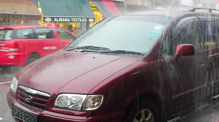 curbside : SINGAPORE - CIRCA AUG 2015: Heavy rain and roof runoff pouring over a parked car on an urban street in Singapore.