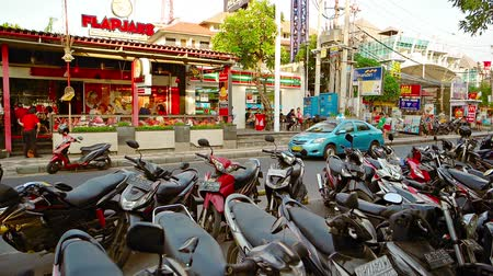 curbside : KUTA. BALI. INDONESIA - CIRCA JUL 2015: Many motorcycles parked curbside on a typical commercial street fronting several local businesses in Kuta. Bali.