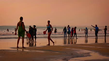 waders : KUTA. BALI. INDONESIA - CIRCA JUL 2015: Beachgoers participating in all kinds of recreational activities. including matkot. swimming and surfing in Kuta. Bali.
