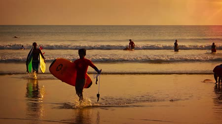 waders : KUTA. BALI. INDONESIA - CIRCA JUL 2015: Tourists wading out of the ocean at sunset. after a long day of surfing in Kuta. Bali.