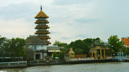 tiered : Cruising past Zhi Zhen Ge Temple from aboard a small boat on the Chao Phraya River in Bangkok. Thailand. Video FullHD Stock Footage