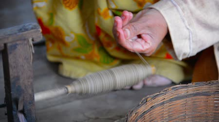 enrolamento : Elderly .Burmese woman winding thread onto a quickly spinning spool as part of a manufacturing process for the production of yarn at a village in Myanmar. Video 1920x1080 Stock Footage