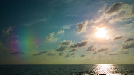 puffy clouds : Late afternoon sunlight Shining through soft puffy clouds over a peaceful. tropical seascape. Video 4k