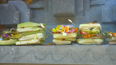 vendégszeretet : Offerings of money. flowers and incense to Hindu gods. presented on a long. cement altar at Tirta Empul Temple in Bali. Indonesia. Video UltraHD