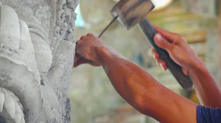 oyma : Asian sculptor. painstakingly chipping away at fine. intricate details of a stone work of art. using a traditional wooden hammer and simple chisel. Video UltraHD