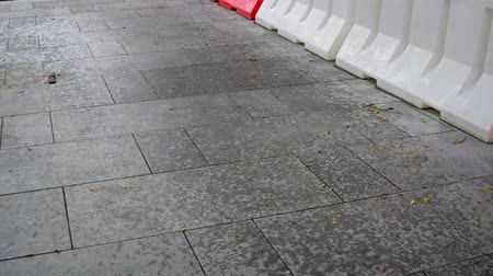 desenli : Partly wet urban walkway with orange and white safety barricades. speckled with rain spots from a brief. seasonal shower. Video UltraHD