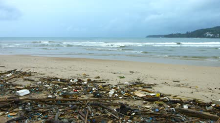 sujo : Sandy tropical beach in Southeast Asia. almost completely covered in litter and garbage. as gentle. tropical waves break on an overcast day. Video UltraHD