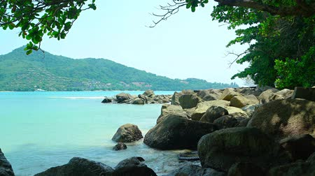 kullancs : Warm waters of a gentle. tropical sea. wash and splash against barnacle encrusted boulders of a natural. rocky beach in Southeast Asia. Video UltraHD