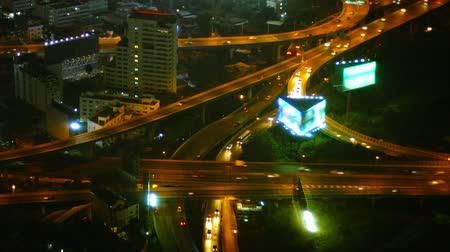 felhőkarcoló : Traffic continues on its relentless course through a complex. multilevel highway junction at night. with lighted billboards and modern highrise buildings.