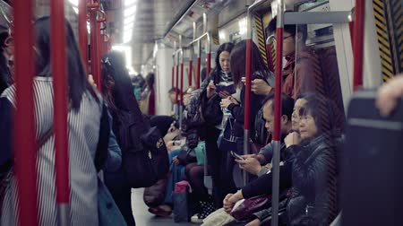 múltiplas : HONG KONG. CHINA - CIRCA JAN 2015: Many commuters. crowded onto a subway car in downtown Hong Kong. at night. Video 3840x2160