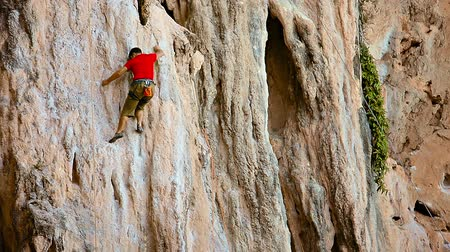 rocks red : AO NANG. THAILAND - CIRCA FEB 2015: Inexperienced rock climber climb up limestone cliff in safety belt on a rope and get guidelines from his instructor. Stock Footage
