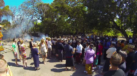 mourners : SANUR. BALI. INDONESIA - CIRCA JUL 2015: Tourists and mourners gather to pay respects at a Hindu cremation ceremony in Sanur. Bali. Indonesia.