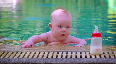 smoczek : Cute and curious baby boy being held by his mother. gazes at his bottle in the cool water of a swimming pool on a sunny day. Video 4k