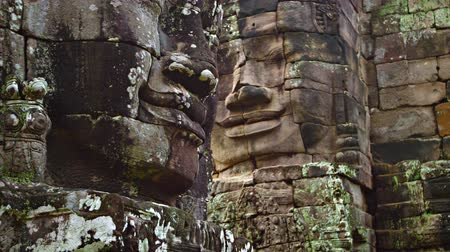 délkelet Ázsia : Ancient. enormous. smiling faces. hand carved from solid stone. standing watch over a courtyard at Bayon Temple near Angkor Thom. Cambodia. Video 3840x2160