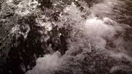 ferahlatıcı : Cool. refreshing water of a natural waterfall tumbles and sprays over large rocks into a foamy pool below. Video 1920x1080