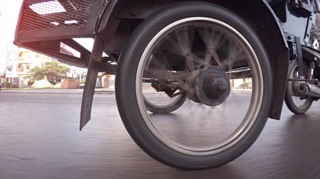improvised : SIEM REAP. CAMBODIA - CIRCA NOV 2015: Wheel of a motor rickshaw spinning as it cruises down a city street. Video UltraHD