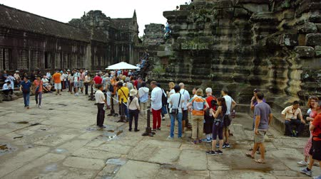 forma : SIEM REAP. CAMBODIA - CIRCA OCT 2015: Tourists form a long line to climb the steps into Angkor Temple near Siem Reap. Cambodia. Video UltraHD Dostupné videozáznamy