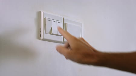 comutar : A mans right hand reaches out to press a wall switch with his index finger. turning off the lights. with sound.