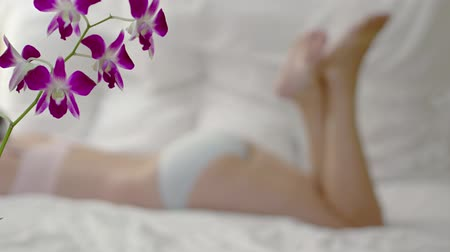 calcinhas : Unfocused shot of a woman in bed. centered on her backside as she kicks her legs. with colorful flowers in the foreground. Video 4k Vídeos