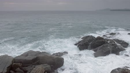 kullancs : Gentle waves and foamy waters wash over barnacle encrusted boulders on a rocky. tropical beach at high tide. Ungraded RAW footage. Video UltraHD