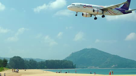 přistání : PHUKET. THAILAND - CIRCA MAR 2016: Commercial airliner passing low over a tropical beach on approach for landing at Phuket International Airport. UltraHD 4k footage Dostupné videozáznamy