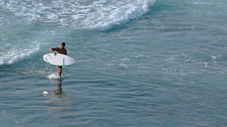 prancha de surfe : BALI. INDONESIA - CIRCA JUL 2015: Tourist carries his surf board as he walks onto the beach in Bali. Indonesia. UltraHD 4k footage